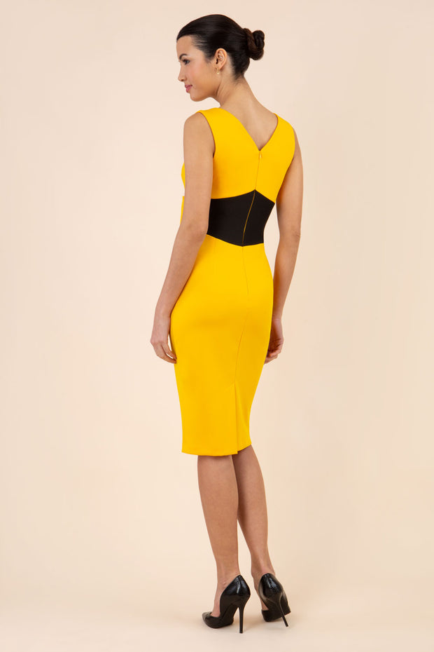 blonde model wearing Diva Catwalk Pencil sleeveless dress with rounded neckline and bow detail at the front with a contrasting black band in saffron yellow back