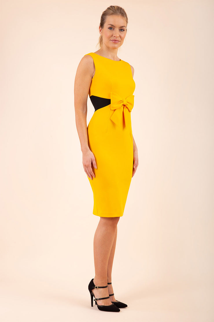blonde model wearing Diva Catwalk Pencil sleeveless dress with rounded neckline and bow detail at the front with a contrasting black band in saffron yellow front