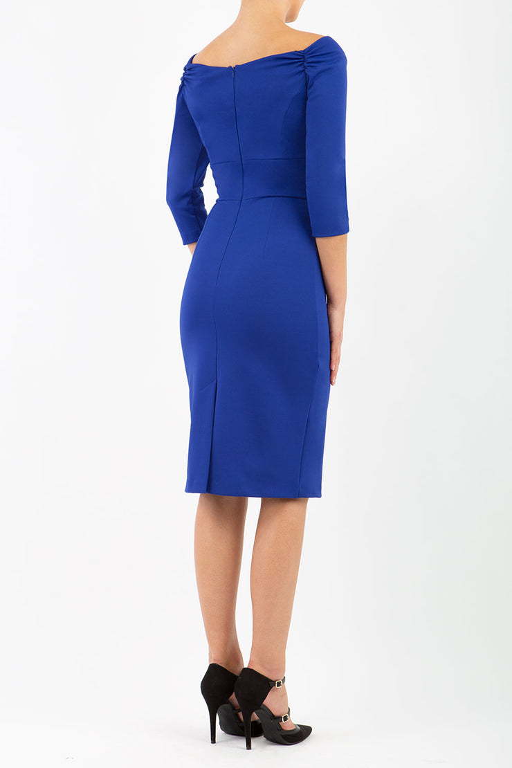brunette model wearing diva alpa cocktail pencil dress in royal blue off shoulder style with sleeves and tie detail on waist knee length back