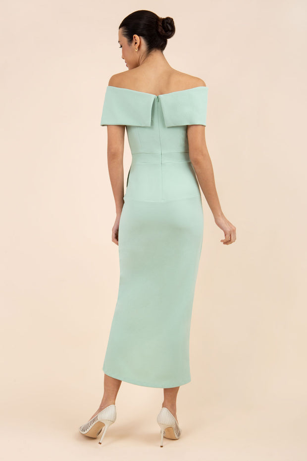 brunette model wearing diva catwalk vegas calf length pale green midaxi dress with wide bardot neckline and open shoulders with a large opening at the front of the skirt with pleating coming down long skirt back