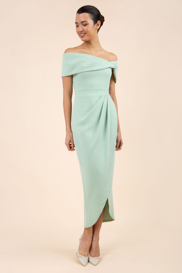 brunette model wearing diva catwalk vegas calf length pale green midaxi dress with wide bardot neckline and open shoulders with a large opening at the front of the skirt with pleating coming down long skirt front