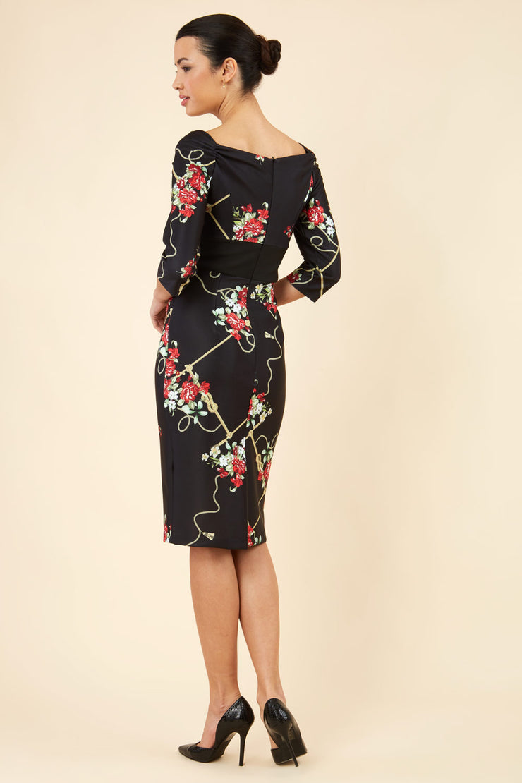 Brunette model is wearing Diva Catwalk Pencil Printed three quarter sleeved dress with wide black band and wide v neckline in Vintage Rose print back