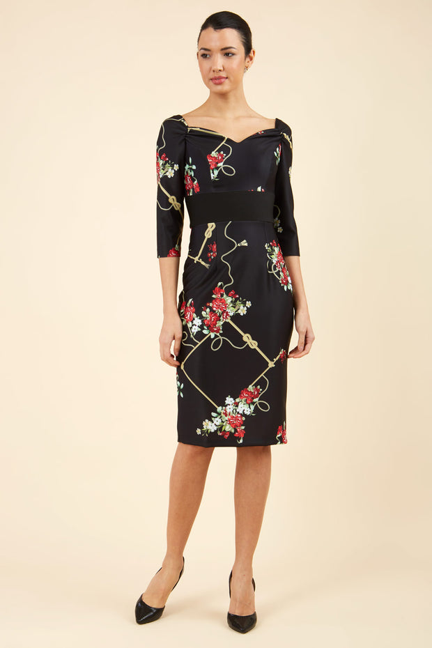 Brunette model is wearing Diva Catwalk Pencil Printed three quarter sleeved dress with wide black band and wide v neckline in Vintage Rose print front