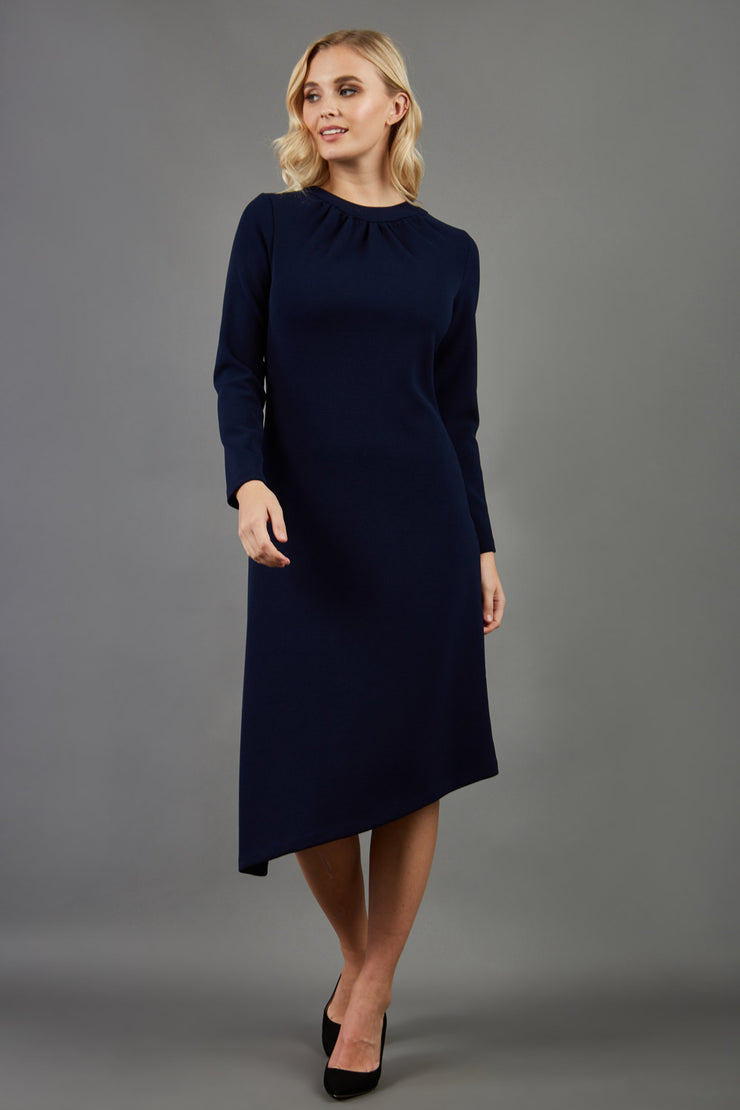 blonde model is wearing diva catwalk dartington asymmetric skirt midaxi long sleeve dress with rounded pleated neckline a-line style in navy blue front
