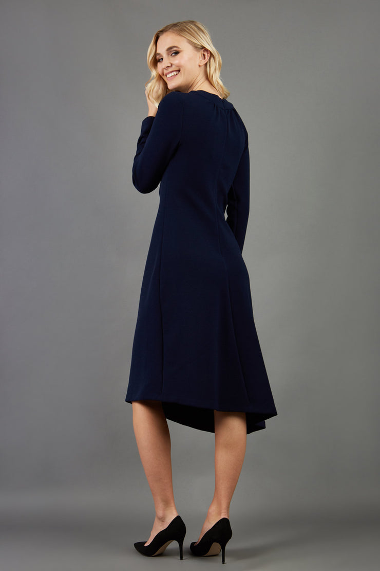 blonde model is wearing diva catwalk dartington asymmetric skirt midaxi long sleeve dress with rounded pleated neckline a-line style in navy blue back