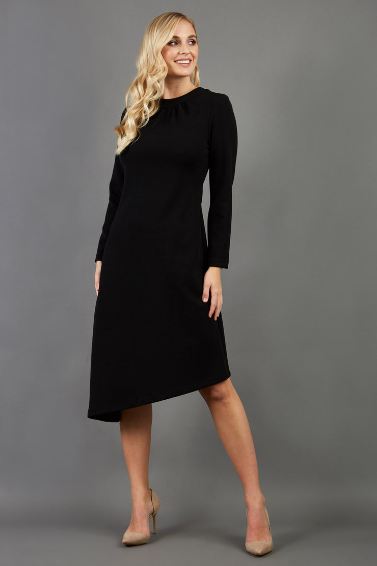 blonde model is wearing diva catwalk dartington asymmetric skirt midaxi long sleeve dress with rounded pleated neckline a-line style in black front