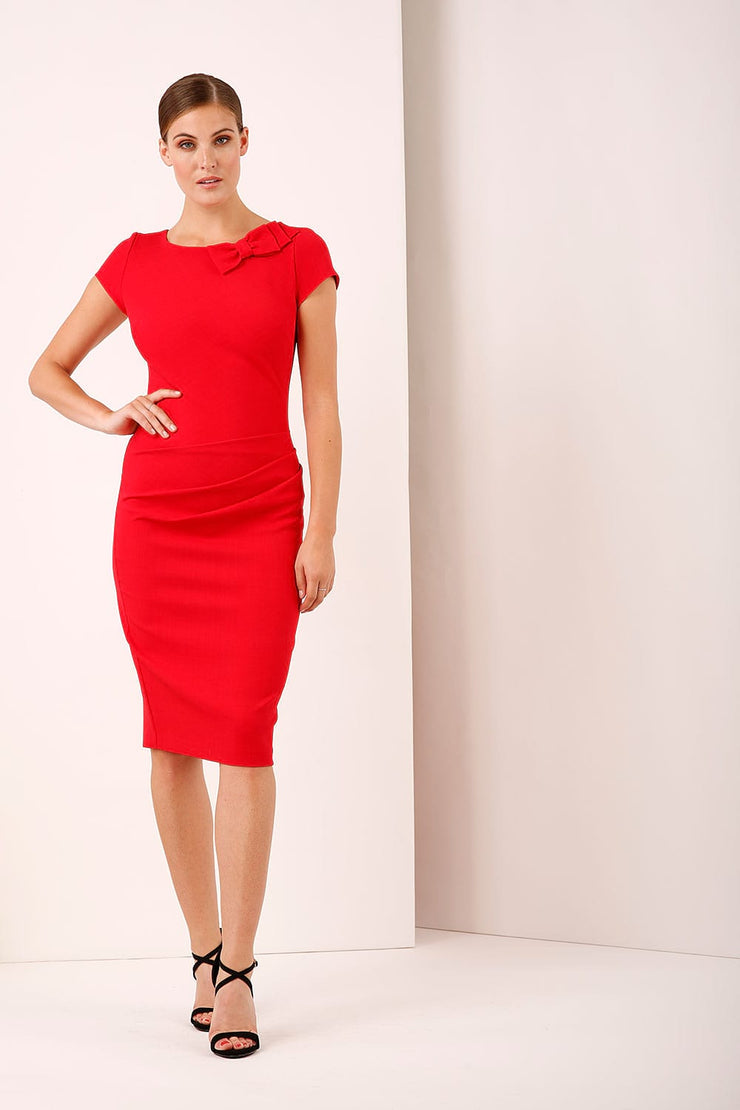 A model wearing a bow detail round neckline pencil knee length dress with pleating detail at the front in red by Diva Catwalk