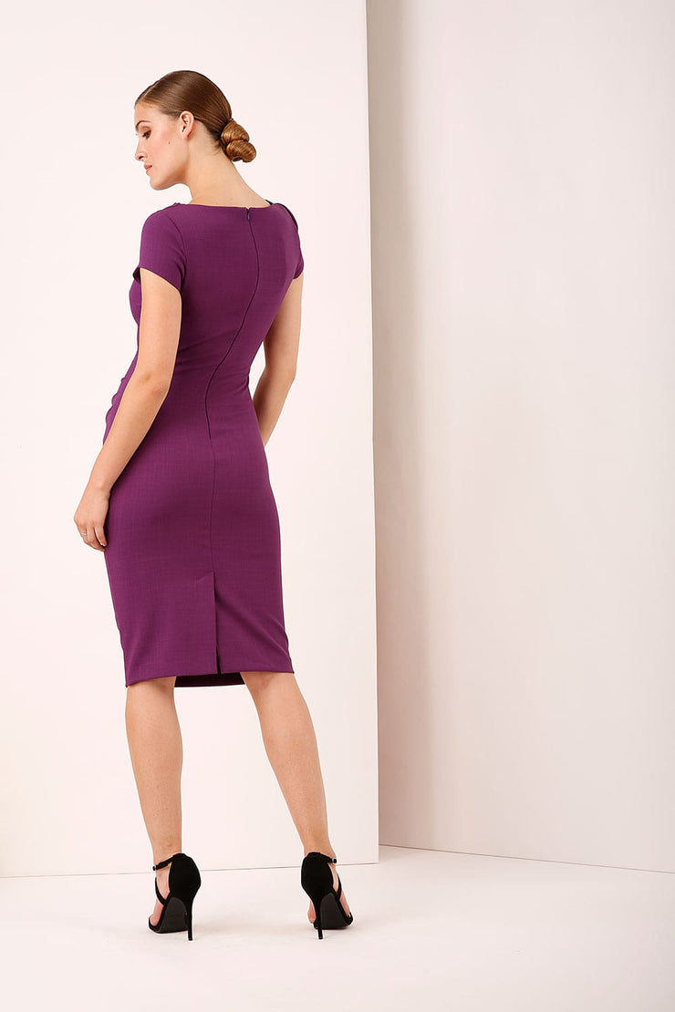A model wearing a bow detail round neckline pencil knee length dress with pleating detail at the front in purple by Diva Catwalk back image