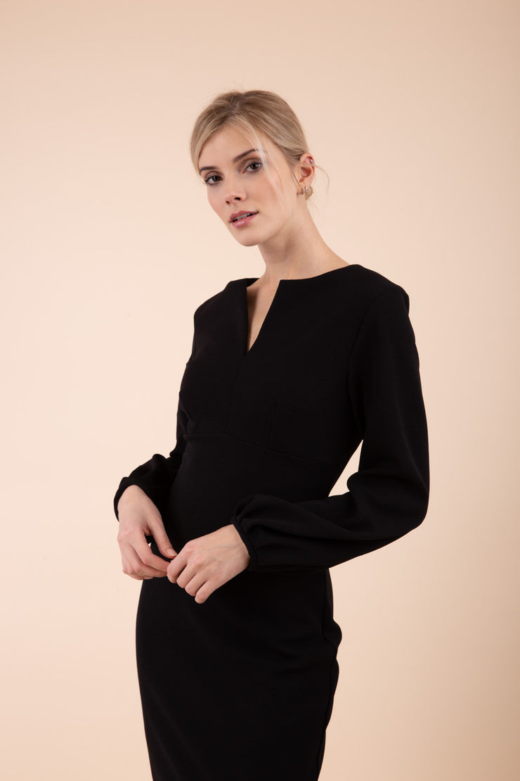 Blonde model wearing Diva Catwalk Praktica long puffed bishop sleeves knee length empire line pencil dress with round neckline with a slit cut in the middle in Black front