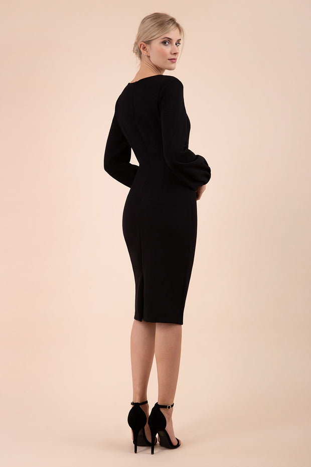 Blonde model wearing Diva Catwalk Praktica long puffed bishop sleeves knee length empire line pencil dress with round neckline with a slit cut in the middle in Black back