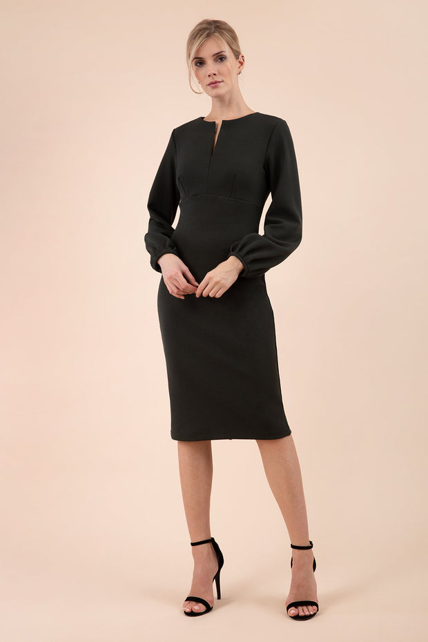 Blonde model wearing Diva Catwalk Praktica long puffed bishop sleeves knee length empire line pencil dress with round neckline with a slit cut in the middle in Deep Green front