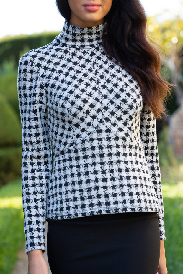 brunette model wearing diva catwalk tamar top with full long sleeve and high neck in dogtooth print front