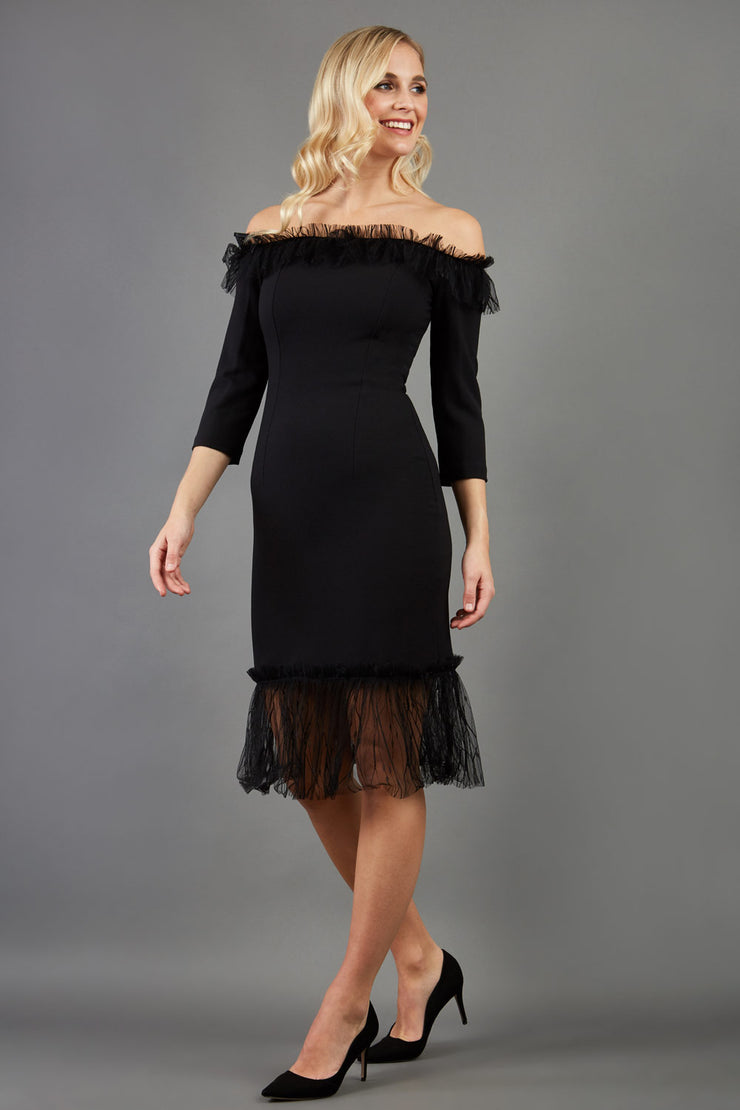 Brunette Model wearing Diva Catwalk Lyrical Pencil Knee length three quarter sleeve off-shoulder Bardot neckline Dress with lace detail around the bottom of the skirt in Black front