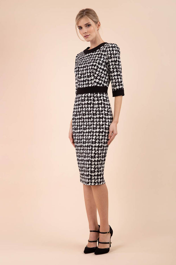 Blonde Model wearing Diva Catwalk Braemar Pencil Dogtooth Print Dress with three quarter sleeve and black band detail around waistline front