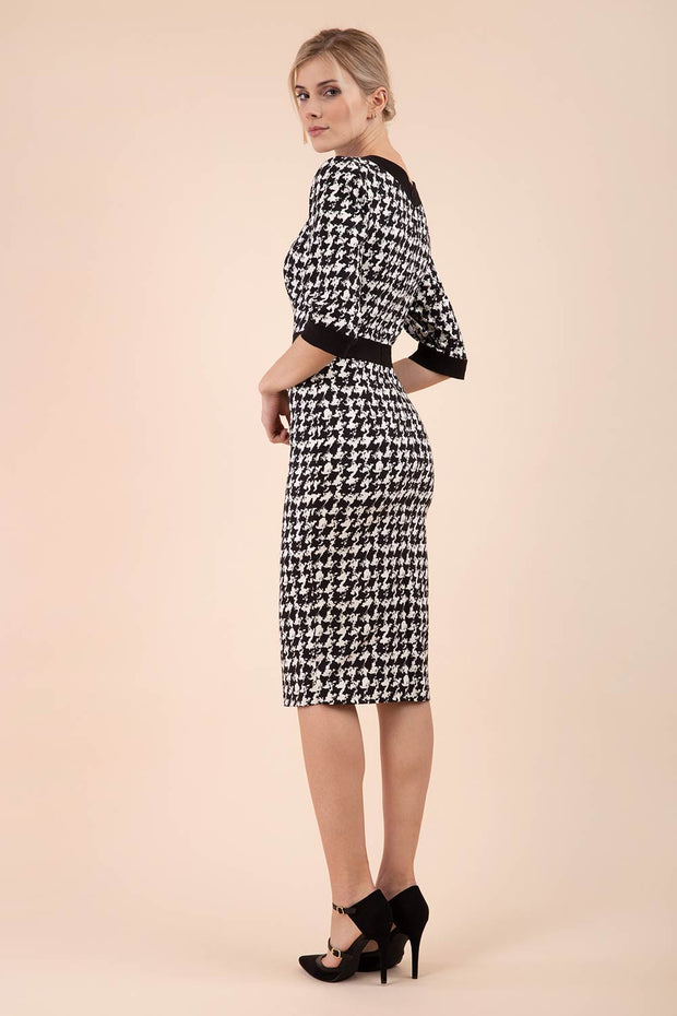 Blonde Model wearing Diva Catwalk Braemar Pencil Dogtooth Print Dress with three quarter sleeve and black band detail around waistline back