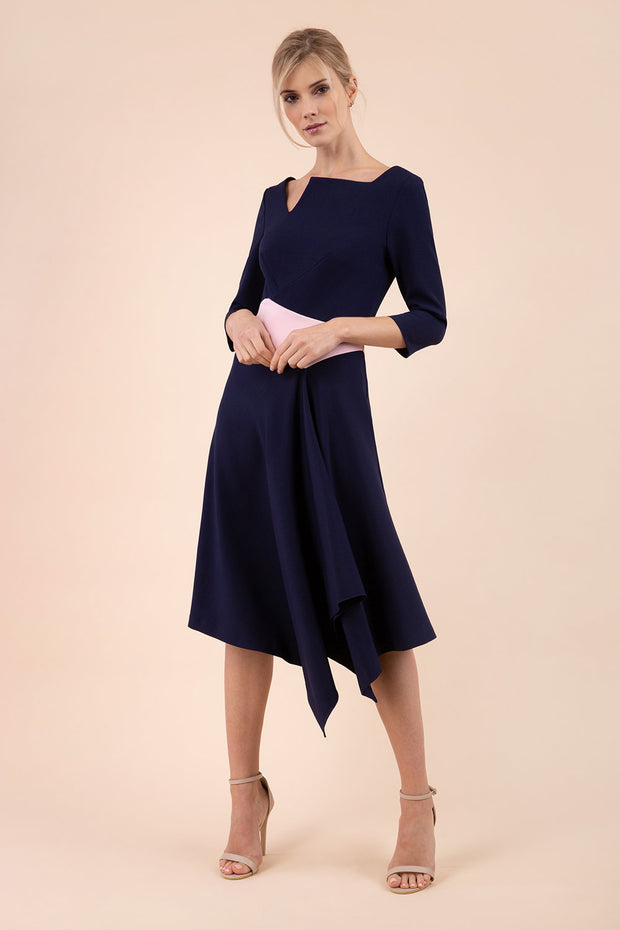 Blonde Model wearing Diva Catwalk Pinto Contrast Swing Dress with asymmetric skirt and asymmetric neckline with three quarter sleeve in Navy Blue front