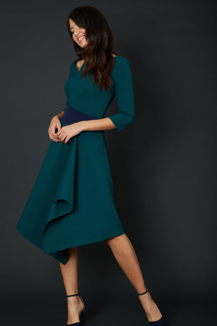 Blonde Model wearing Diva Catwalk Pinto Contrast Swing Dress with asymmetric skirt and asymmetric neckline with three quarter sleeve in Forest Green front