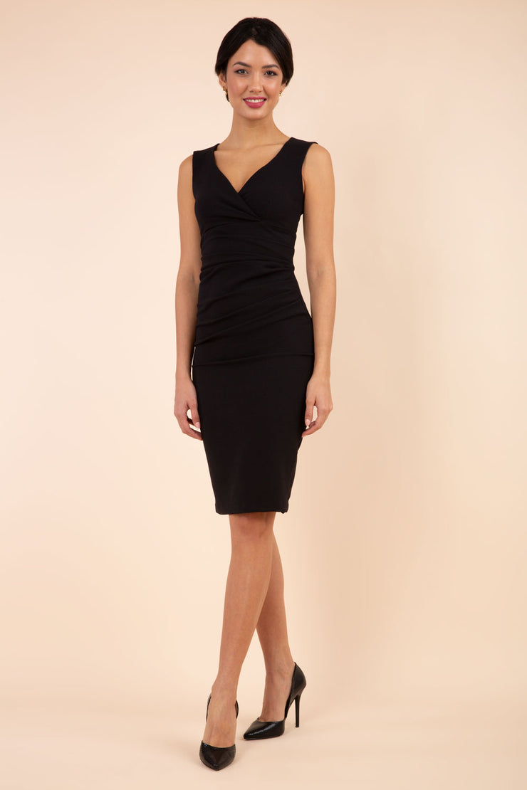 brunette model wearing diva catwalk pencil-skirt black dress with v-neckline and pleating across the tummy without sleeves front