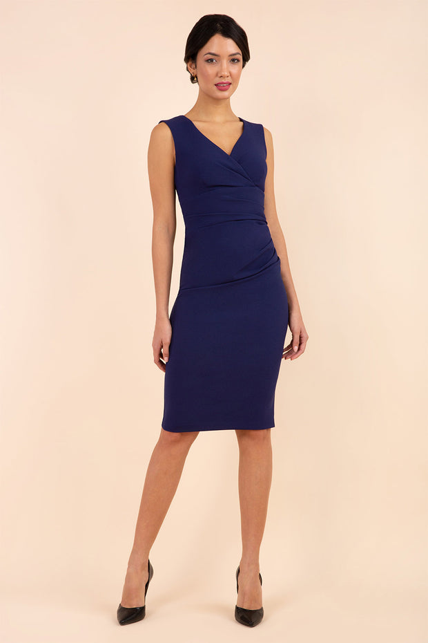 brunette model wearing diva catwalk pencil-skirt blue dress with v-neckline and pleating across the tummy without sleeves front