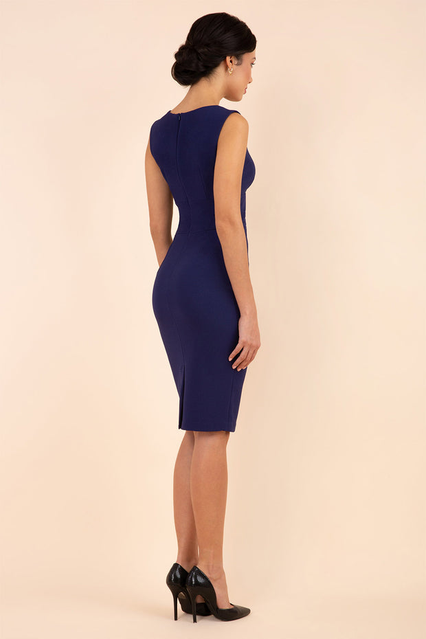 brunette model wearing diva catwalk pencil-skirt blue dress with v-neckline and pleating across the tummy without sleeves back