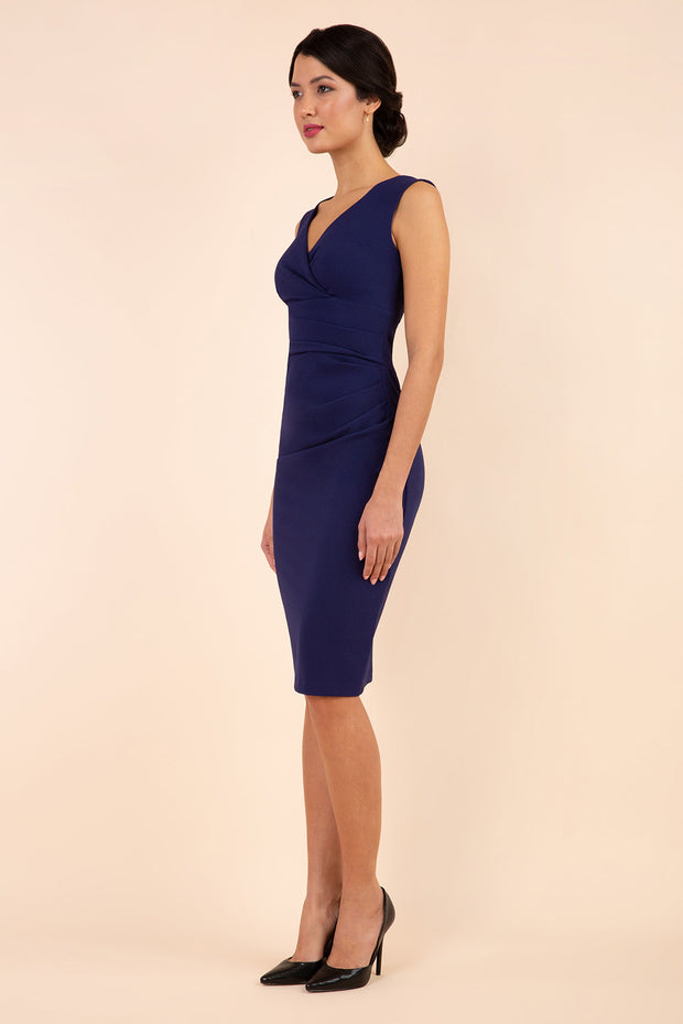 brunette model wearing diva catwalk pencil-skirt navy blue dress with v-neckline and pleating across the tummy without sleeves front