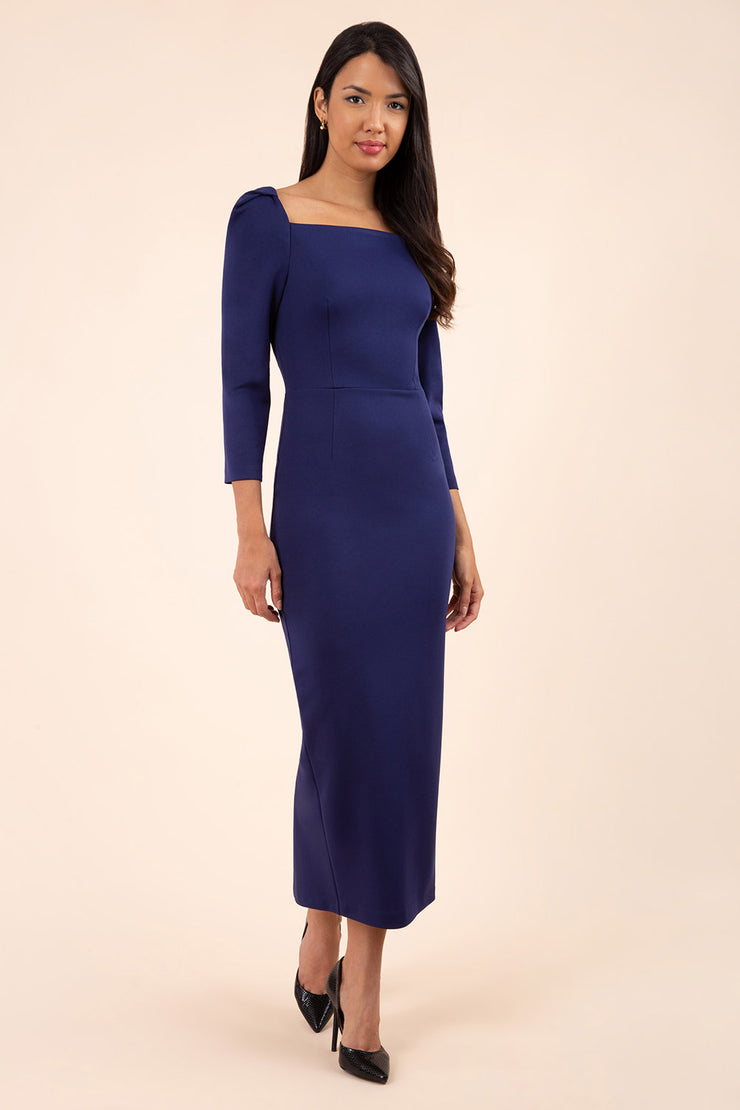 brunette model wearing diva catwalk maxi plain three quarter sleeve dress with pleating on shoulders and square neckline in navy blue front