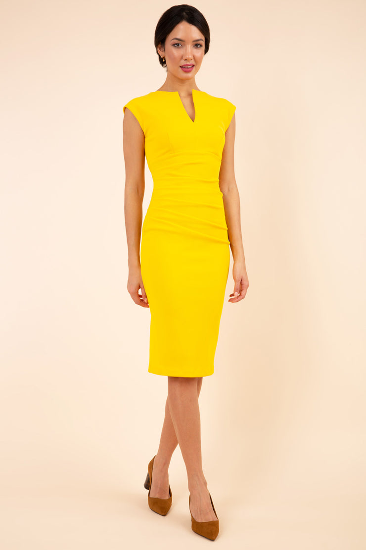 brunette model wearing diva catwalk lydia sleeveless pencil flattering fitted plain dress with split neckline and pleating across the body in spectra yellow front