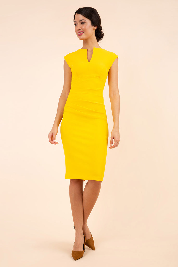 brunette model wearing diva catwalk lydia sleeveless pencil flattering fitted plain dress with split neckline and pleating across the body in saffron yellow front