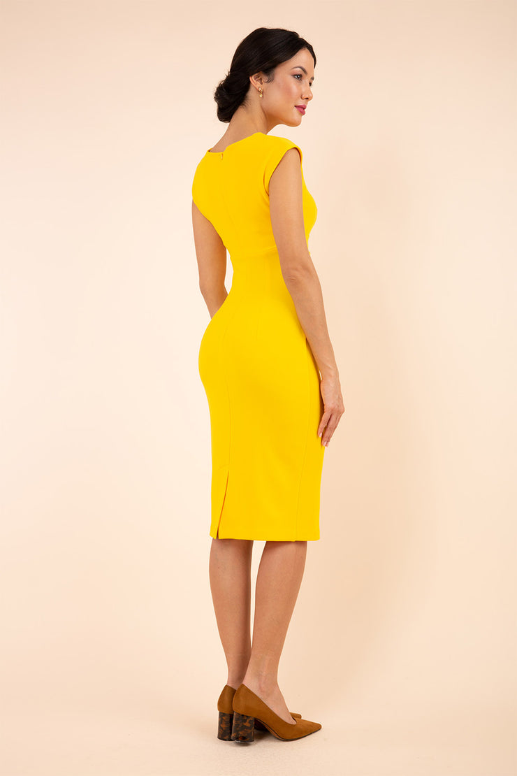 brunette model wearing diva catwalk lydia sleeveless pencil flattering fitted plain dress with split neckline and pleating across the body in spectra yellow back