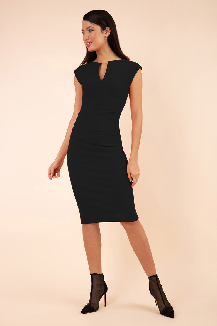 brunette model wearing diva catwalk lydia sleeveless pencil flattering fitted plain dress with split neckline and pleating across the body black front