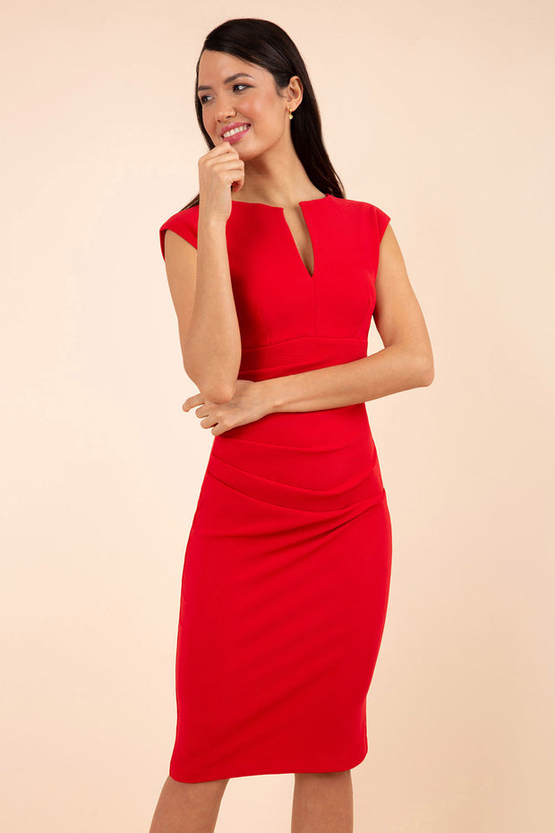 brunette model wearing diva catwalk lydia sleeveless pencil flattering fitted plain dress with split neckline and pleating across the body true redl front