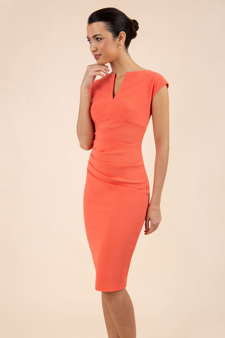 brunette model wearing diva catwalk lydia sleeveless pencil flattering fitted plain dress with split neckline and pleating across the body sea coral front