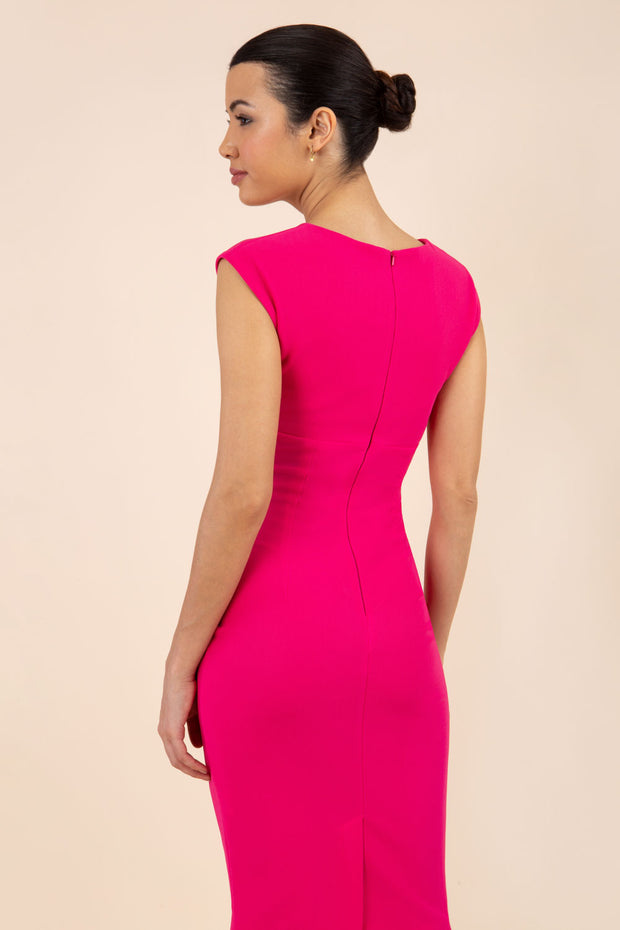 brunette model wearing diva catwalk lydia sleeveless pencil flattering fitted plain dress with split neckline and pleating across the body in pink back