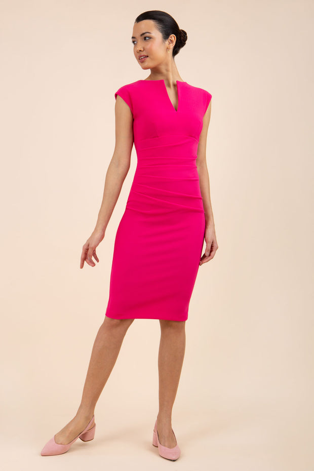 brunette model wearing diva catwalk lydia sleeveless pencil flattering fitted plain dress with split neckline and pleating across the body in pink front