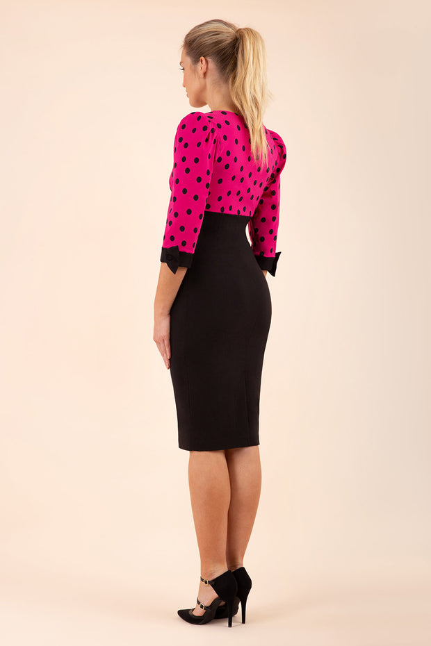 blonde model wearing diva catwalk bristow vintage three quarter sleeve pencil floral dress with low v neckline and puffed shoulders in pink polka dot top and black back
