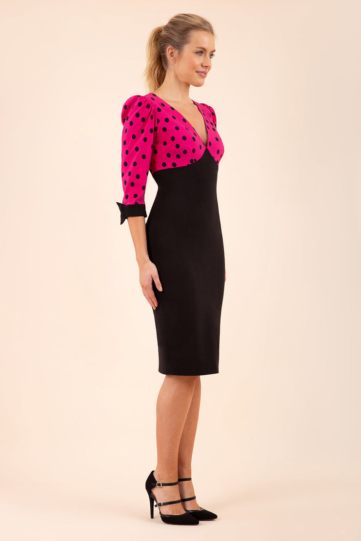 blonde model wearing diva catwalk bristow vintage three quarter sleeve pencil floral dress with low v neckline and puffed shoulders in pink polka dot top and black front