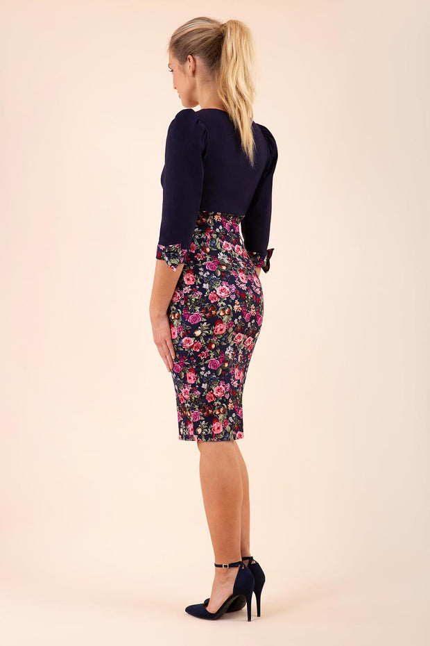 blonde model wearing diva catwalk bristow vintage three quarter sleeve pencil floral dress with low v neckline and puffed shoulders in navy top back