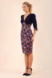 blonde model wearing diva catwalk bristow vintage three quarter sleeve pencil floral dress with low v neckline and puffed shoulders in navy top front