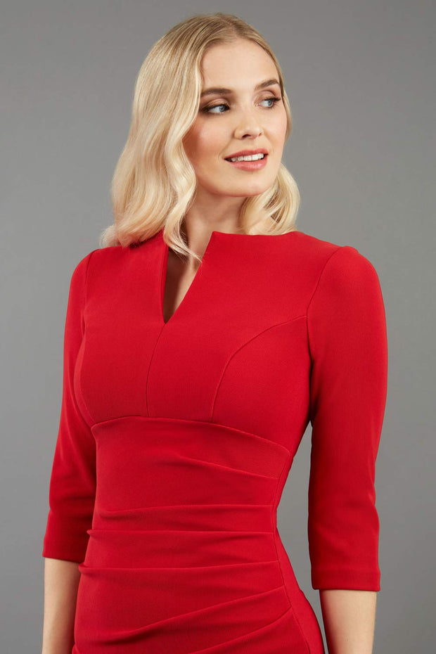 model wearing Diva Catwalk pencil three quarter sleeve dress with a split neckline and pleating across the tummy in red front