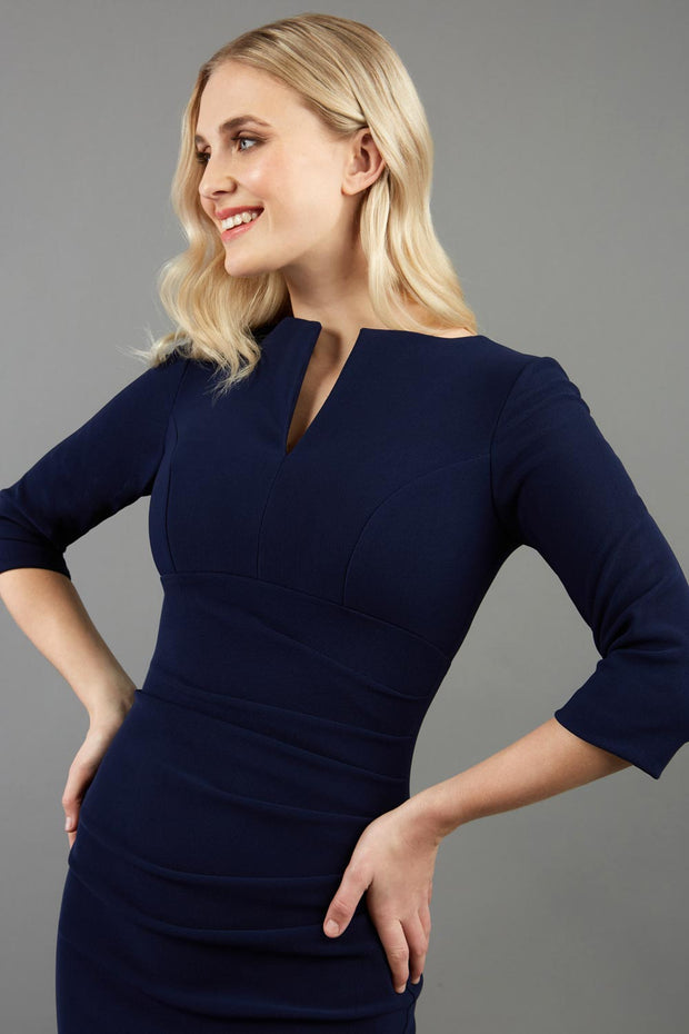model wearing Diva Catwalk pencil three quarter sleeve dress with a split neckline and pleating across the tummy in navy front