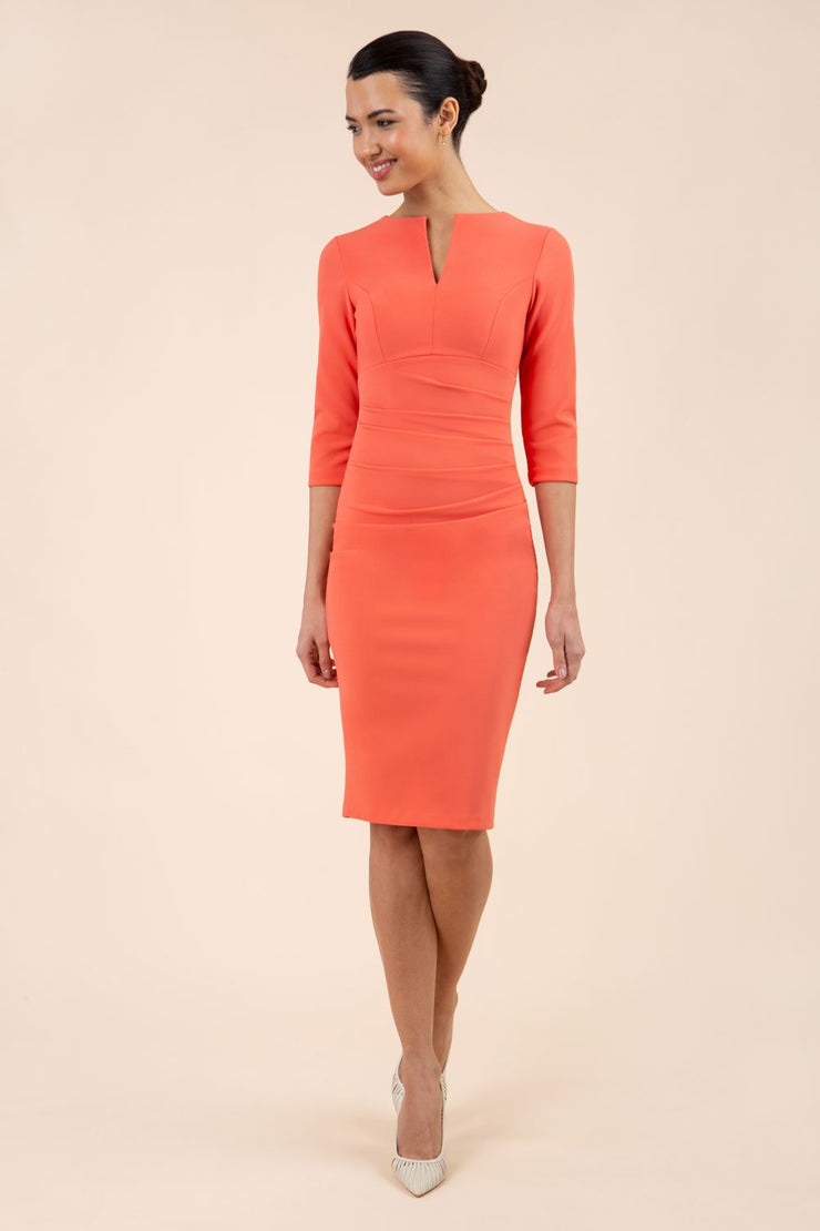 brunette model wearing diva catwalk best selling lydia pencil sleeved dress with slit at the neckline and pleating across the tummy in colour sea coral front