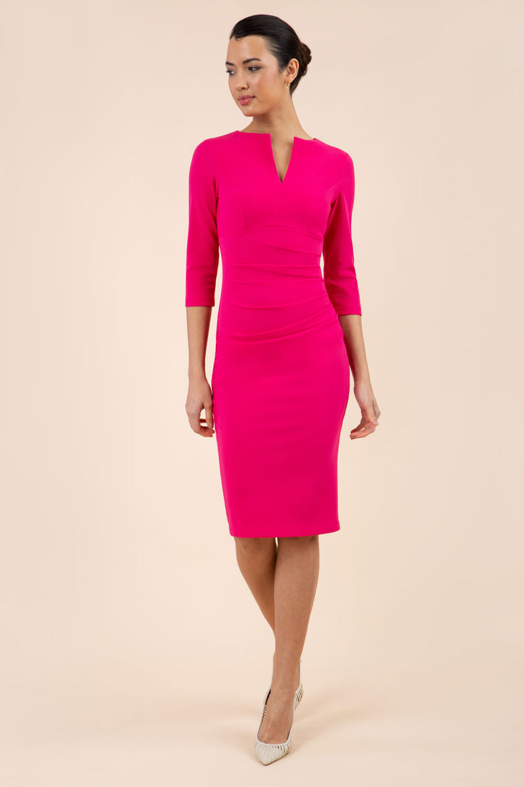 model wearing Diva Catwalk pencil three quarter sleeve dress with a split neckline and pleating across the tummy in pink front