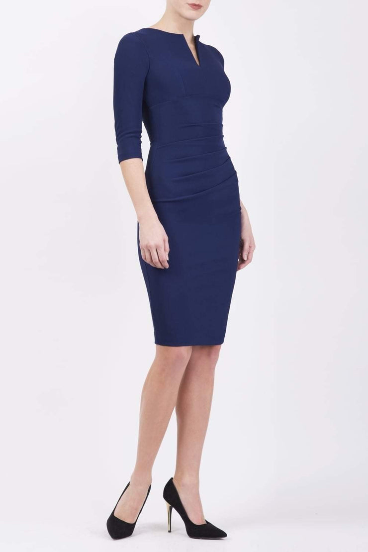 model wearing Diva Catwalk pencil three quarter sleeve dress with a split neckline and pleating across the tummy in navy Blue front