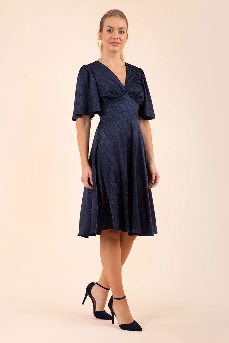 brunette model wearing diva catwalk cambrian satin swing dress with bell short sleeve wide asymmetric waistband and pleating under bust and low v-neckline in navy front