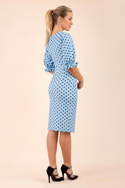 Blonde model wearing Diva Catwalk Palacio Pencil dress v neckline and pleating across the tummy with puffed short sleeves in blue polka dot back