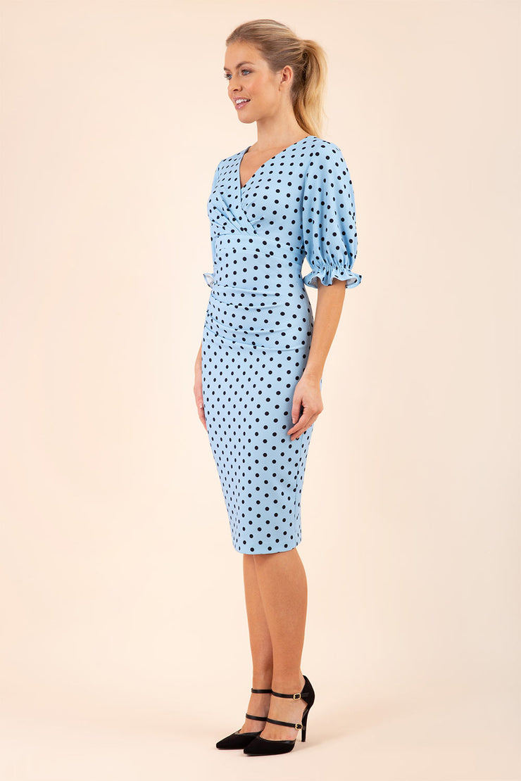 Blonde model wearing Diva Catwalk Palacio Pencil dress v neckline and pleating across the tummy with puffed short sleeves in blue polka dot front