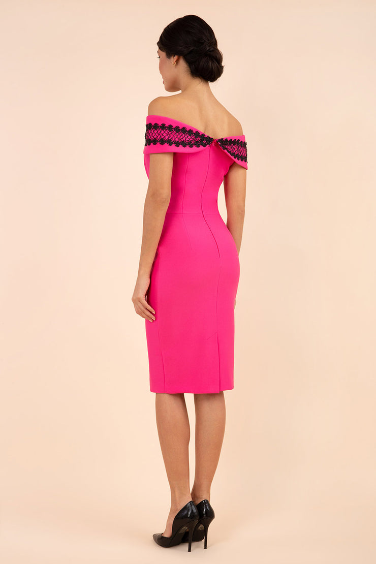 brunette model wearing diva catwalk kurumba pencil dress with bardot off shoulder neckline and lace detail across it in hibiscus pink and black colour back
