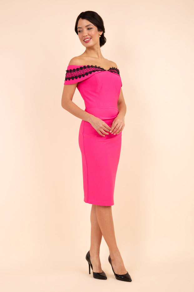 brunette model wearing diva catwalk kurumba pencil dress with bardot off shoulder neckline and lace detail across it in pink and black colour front