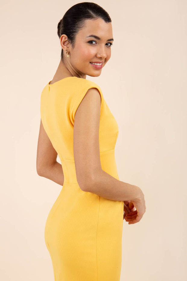 brunette model wearing Diva catwalk Suzy pencil sleeveless dress with v-neckline and wide wasteland in radiant yellow back