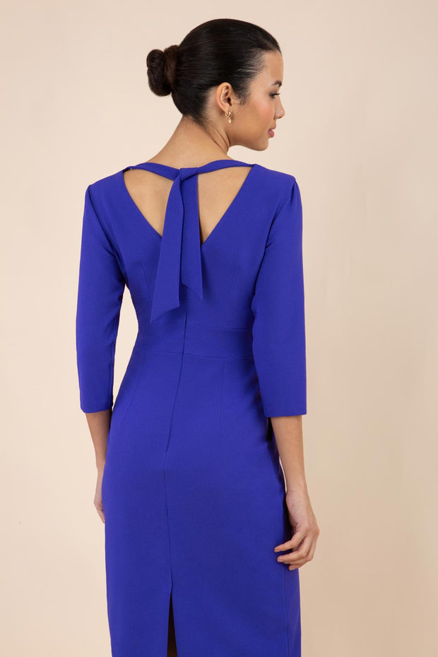 brunette model wearing diva catwalk wimpole a-line flattering dress with lowered v-neck at the back and tie detail and three quarter sleeve and and widened skirt with vent  in spectrum indigo back